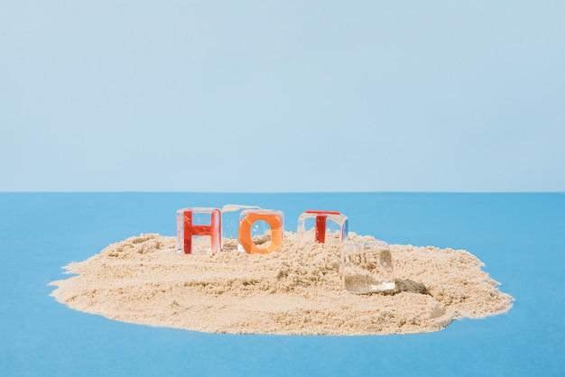 Lettres congelées dans des glaçons transparents sur une île d'été. concept abstrait minimal. fond bleu.