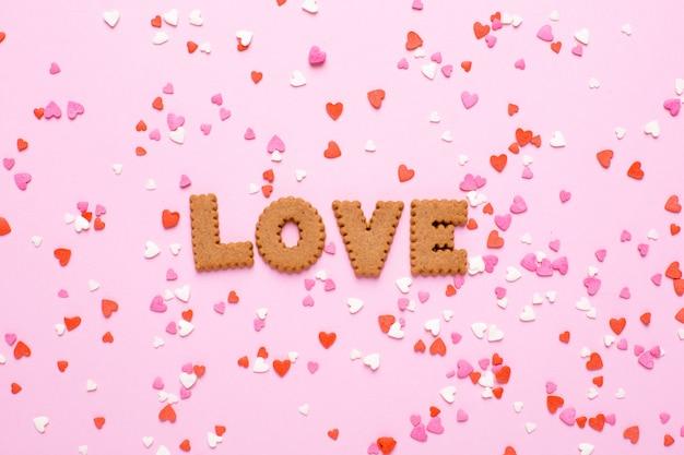 Lettres cookies je t'aime avec des coeurs roses et rouges sur rose