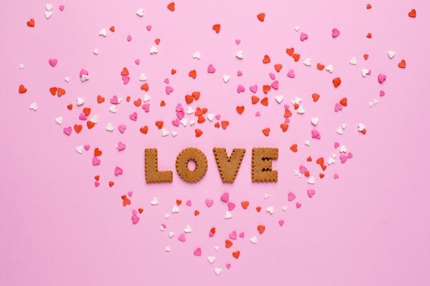 Lettres cookies love avec des coeurs roses et rouges sur rose