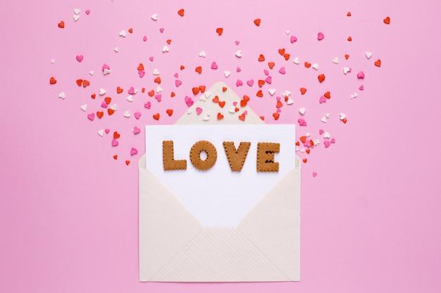 Lettres cookies love avec enveloppe et coeurs rouges sur rose