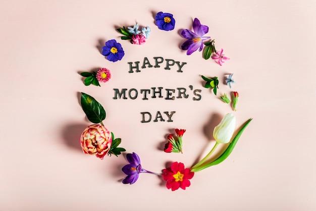 Lettres de la fête des mères heureux avec différentes fleurs de printemps autour d'eux