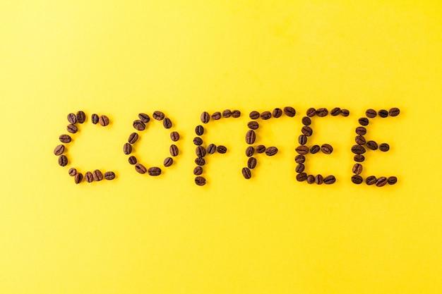 Lettres grains de café sur fond jaune vibrant. minimalisme food morning energy concept.