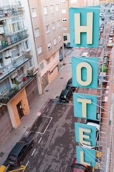 Lettres d'hôtel verticales fixées sur le bâtiment avec une vraie rue de la ville à l'envers