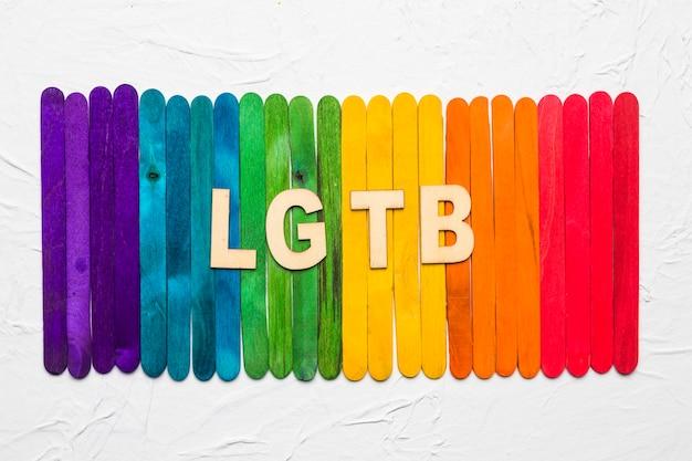 Lettres lgbt sur fond de bâtons de bois colorés