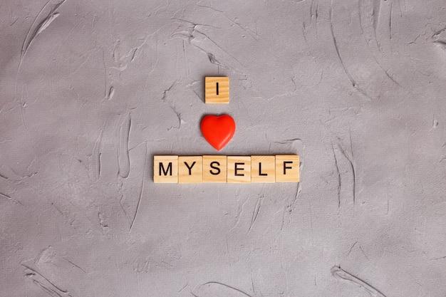 Lettres majuscules en bois avec citation écrite: je m'aime. concept de m'accepter.