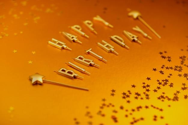 Lettres d'or joyeux anniversaire sur un fond d'or avec des étoiles.