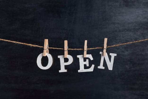 Des lettres sous forme de mot ouvert sont accrochées à une pince à linge. ouverture du pressing. heures d'ouverture.