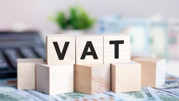 Les lettres tva sur les cubes de bois, les billets et la calculatrice en arrière-plan. tva - abréviation de taxe sur la valeur ajoutée. concept d'entreprise.