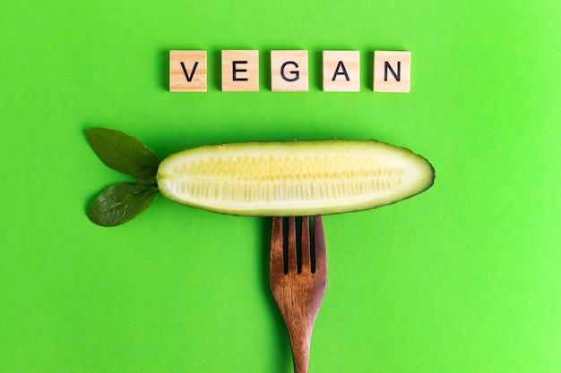 Lettres végétaliennes végétaliennes concombre écologique plus sain sur une fourchette en bois sur une surface verte