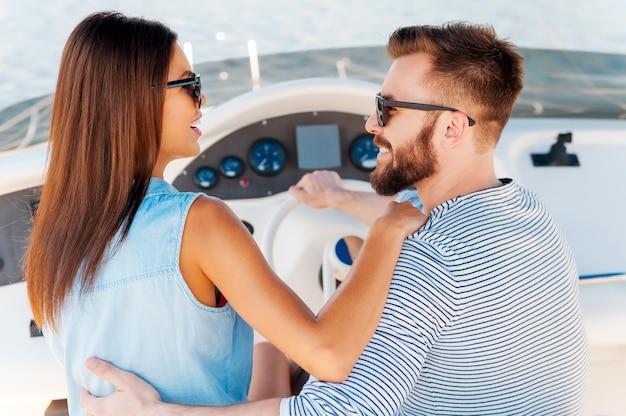 Leur amour est plus grand que l'océan. heureux jeune couple se regardant et souriant en conduisant un yacht