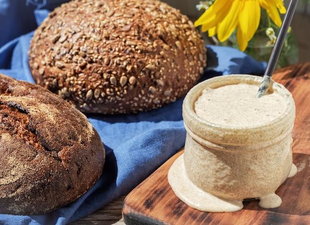 Levain pour pain dans un bocal en verre et pains faits maison