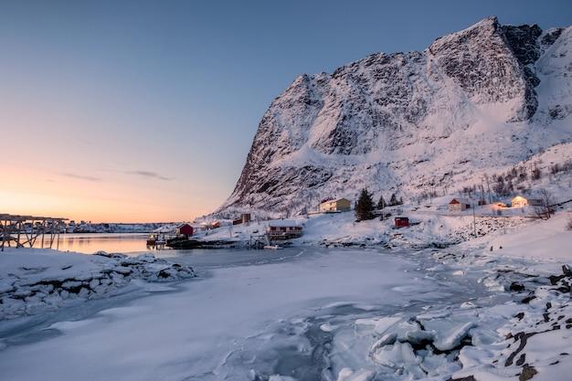 Lever du soleil sur l'archopel des lofoten avec un village scandinave dans la vallée