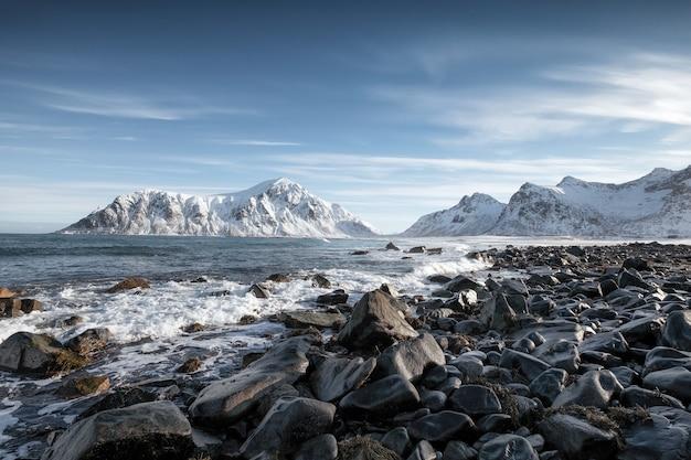 Lever du soleil bleu de la chaîne de montagnes de neige avec des vagues frappant le littoral à la plage de skagsanden, îles lofoten