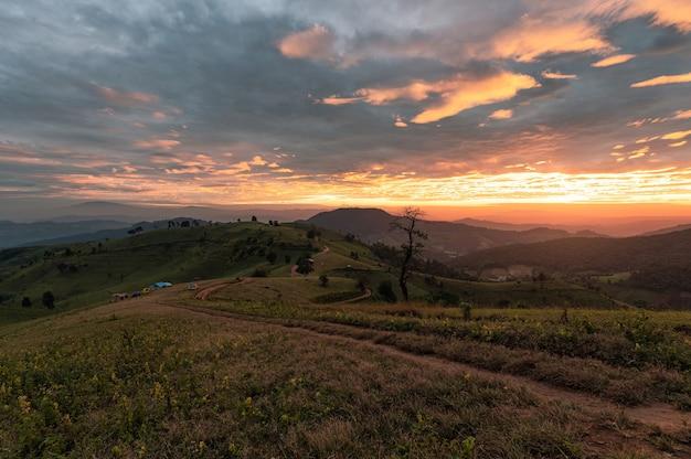 Lever du soleil sur la colline des terres agricoles avec ciel coloré et touristes camping en vacances dans le parc national à doi mae tho, chiang mai