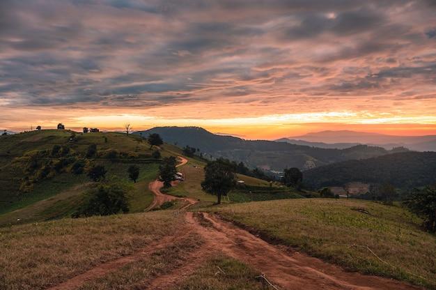 Lever du soleil sur la colline des terres agricoles avec ciel coloré et touristes camping en vacances dans le parc national à doi mae tho