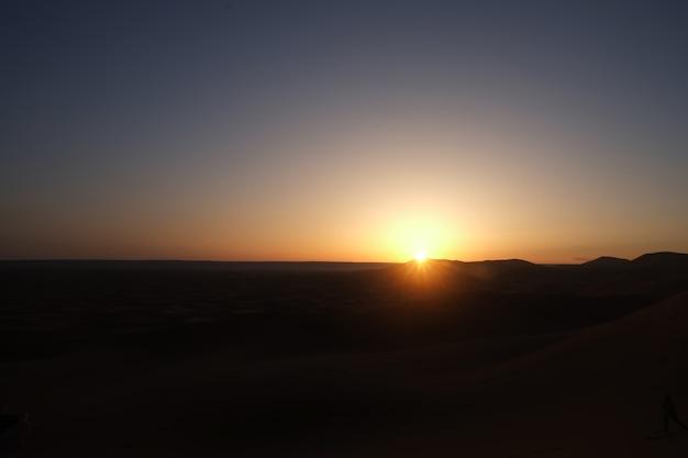 Lever du soleil dans le désert du sahara. merzouga, maroc.