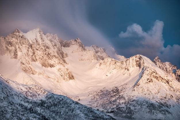 Lever du soleil doré sur la montagne de neige avec des nuages qui souffle sur la crête