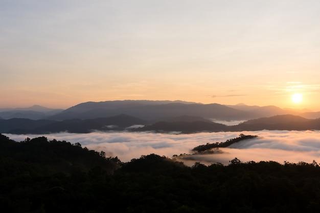 Lever du soleil sur les grandes montagnes et la couverture brumeuse sur la forêt.