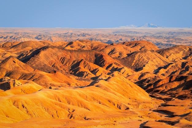 Le lever du soleil illumine la vallée de la lune jaune. paysage désertique en afrique. namibie