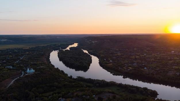 Lever du soleil en moldavie, village avec église orthodoxe, rivière se divisant en deux parties