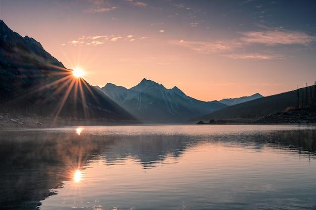 Lever du soleil sur la montagne avec du brouillard dans le lac medicine à jasper