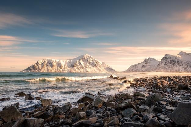 Lever du soleil sur la montagne de neige au littoral à la plage de skagsanden