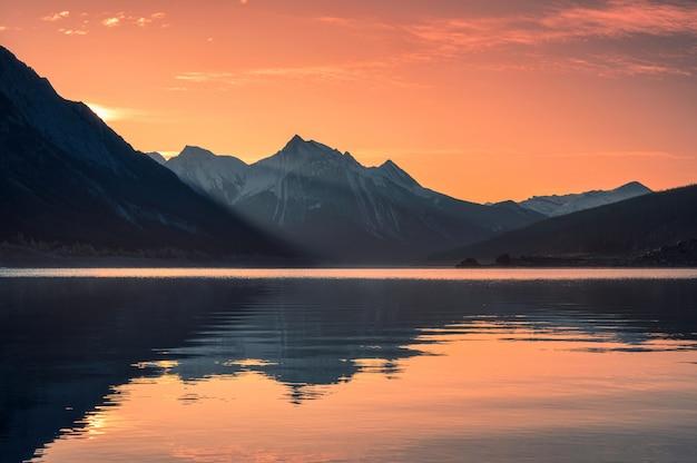 Lever du soleil sur les montagnes rocheuses avec ciel coloré sur medicine lake, parc national de jasper