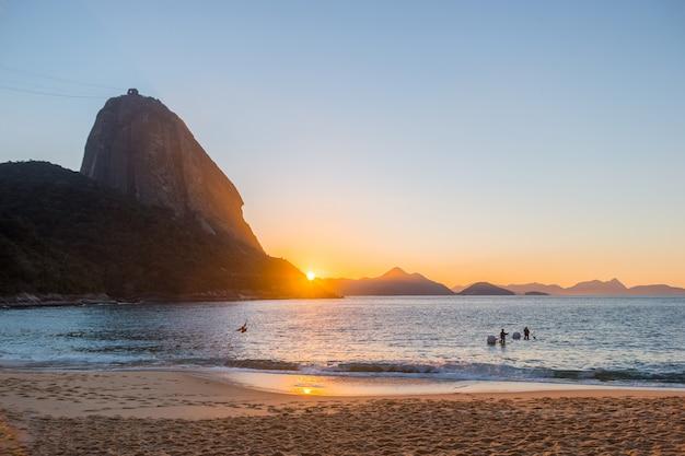 Lever du soleil sur la plage rouge du quartier urca à rio de janeiro au brésil.
