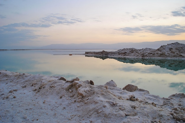 Lever du soleil sur le rivage de la mer morte en israël. l'endroit le plus bas de la terre. cristaux de sel au lever du soleil