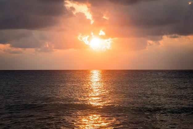Lever du soleil à travers les nuages de pluie de new smyrna beach, floride usa. les vagues battent l'écume de la mer sur le sable de la plage. vue spectaculaire sur le lever du soleil du matin dans le ciel nuageux.