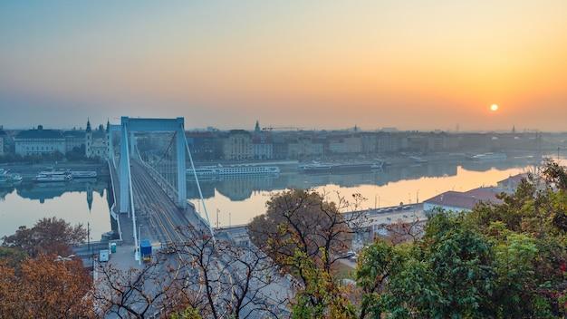 Lever du soleil sur la ville de budapest, le danube et le pont elizabeth en saison d'automne