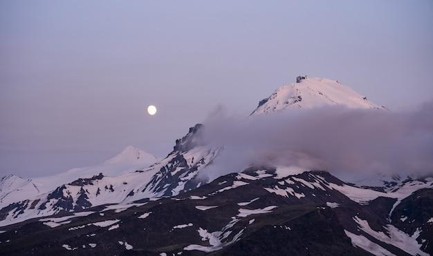 Lever de soleil coloré au sommet d'un grand volcan avec vue sur les nuages. nuances de rose, violet et orange avec la silhouette des montagnes.