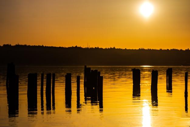 Un lever de soleil doré sur une colline se reflétant sur l'eau