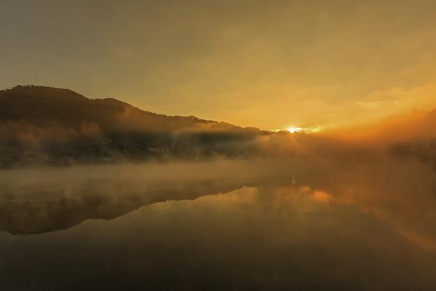 Lever de soleil matin brumeux sur montagne avec village autour de la rivière