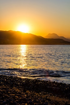 Le lever de soleil orange sous les montagnes et la mer
