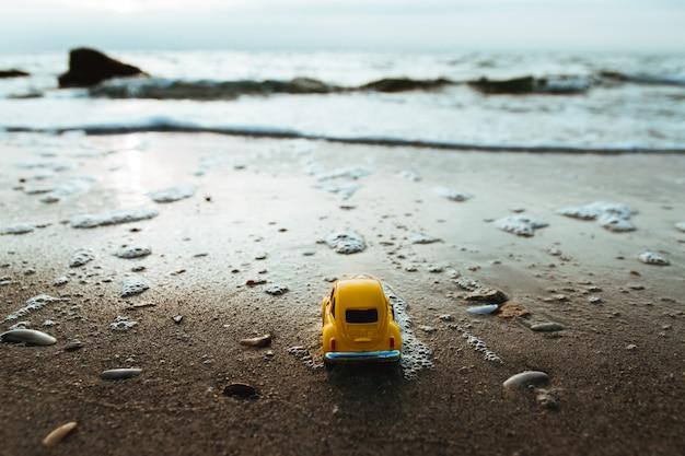 Lever de soleil sur la plage de l'île tropicale et miniature de voiture.