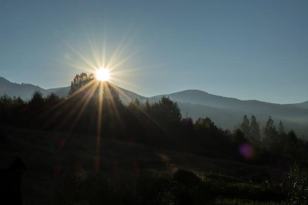 Lever de soleil sur le sommet de la montagne. rayons inondant une vallée brumeuse