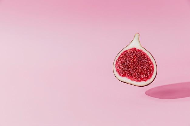 Lévitation de moitié de fruit de figue fraîche et savoureuse avec ombre sur fond rose. coupe transversale de figue tombant ou volant. concept de désert végétalien. ombre de voler des aliments sains. photo colorée de haute qualité