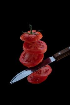 Lévitation de tomates fraîchement coupées. un couteau coupe la tomate en l'air. tranches de tomates volantes isolés