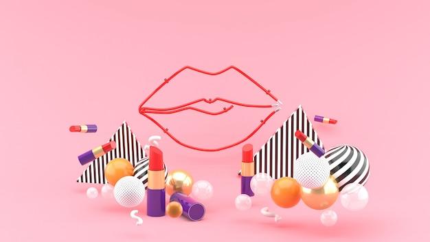 Lèvre au milieu d'un rouge à lèvres et boules colorées sur un espace rose