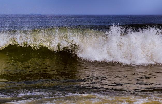 La lèvre de curling ondulante aux vagues océaniques se brise sur des barres de sable peu profondes.