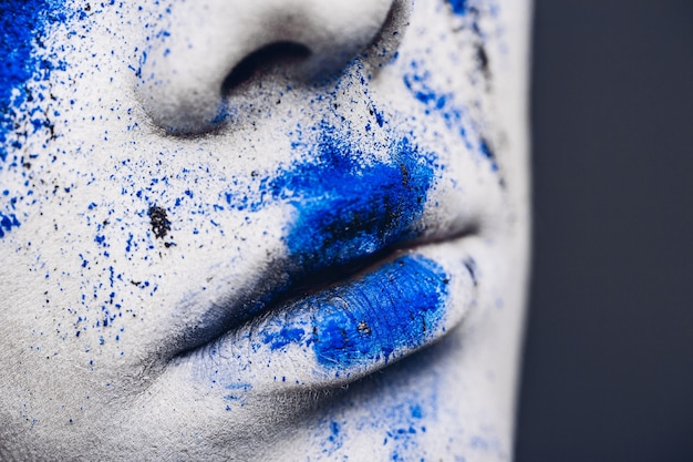 Lèvres de femme avec maquillage en poudre colorée.