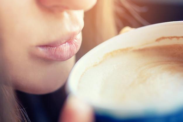 Les lèvres fille touchent la tasse avec du café.