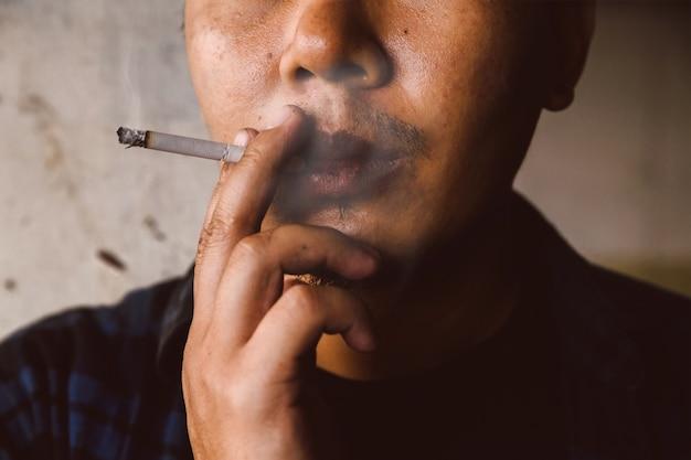 Lèvres noires de l'homme, fumeur.effets de fumer
