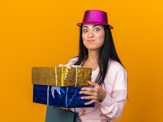 Lèvres pinçantes jeune belle femme portant un chapeau de fête tenant un sac-cadeau avec des coffrets cadeaux isolés sur un mur orange