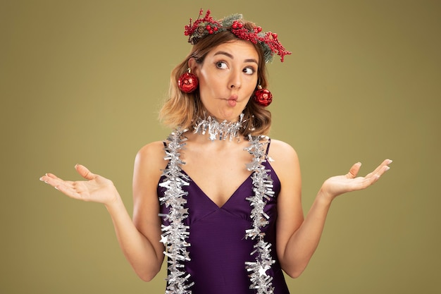 Lèvres pinçantes jeune belle fille vêtue d'une robe violette et d'une couronne avec une guirlande sur le cou tenant des boules de sapin de noël sur les oreilles et écartant les mains isolées sur fond vert olive