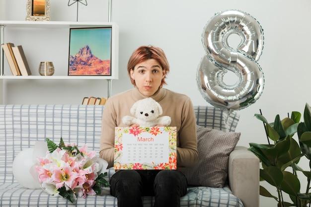 Lèvres pincées beau mec le jour de la femme heureuse tenant un ours en peluche avec un calendrier assis sur un canapé dans le salon