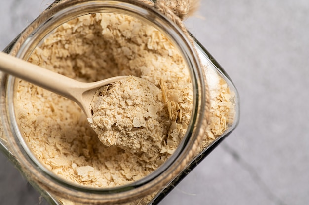 Levure nutritionnelle en flocons avec une cuillère en bois et un bocal en verre sur fond gris