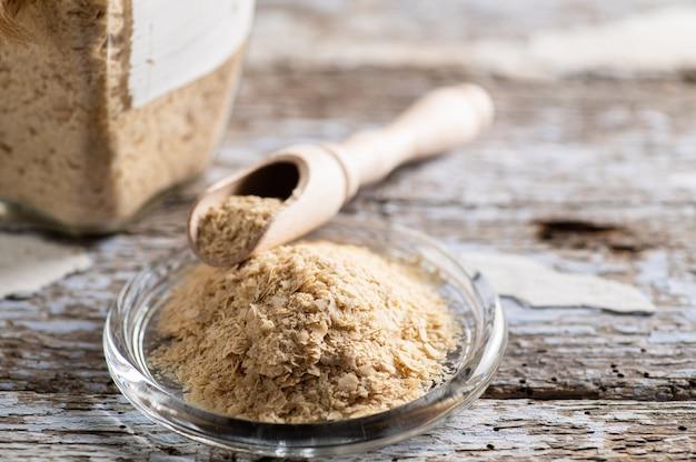 Levure nutritionnelle en flocons dans une assiette sur fond de bois