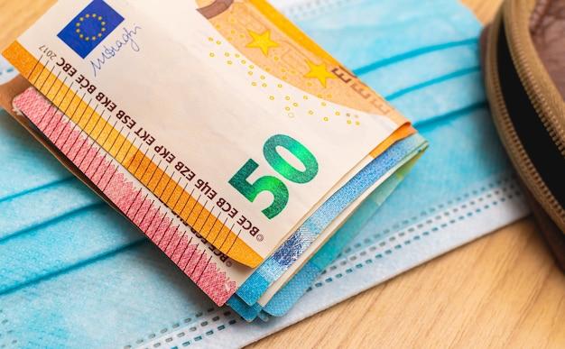 Une liasse de billets en euros sur un masque chirurgical bleu pour le concept d'économie pendant la pandémie de covid